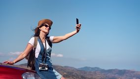 Pleasant happy travel woman enjoying journey at mountain landscape taking selfie using smartphone. Pleasant happy travel woman enjoying car journey posing at stock footage