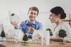 Pleasant happy woman pointing at the house model stock photos