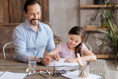 Pleasant inspired father painting sky with his daughter. Inspiration vibes. Happy loving father sitting next to his sweet little daughter and helping her to Royalty Free Stock Image