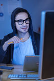 Pleasant intelligent programmer holding a pencil. Creativity and innovation. Pleasant intelligent handsome man holding a pencil and using a tablet while having Stock Photo