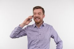 Joyful happy man talking on the phone. Pleasant interaction. Joyful happy man smiling while talking on the phone Royalty Free Stock Image