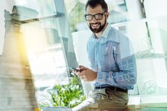 Pleasant joyful man using the smartphone and looking straight. Friendly employee. Pleasant bespectacled joyful man sitting on the table using the smartphone and Stock Photos