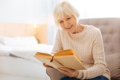 Pleasant kind aged woman smiling and reading a lovely book stock photo