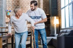 Pleasant kind volunteer supporting a senior man and helping him while walking. Helping hand. Young attentive careful volunteer looking calm while helping an old Royalty Free Stock Photo