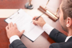 Pleasant lawyer signing papers Stock Photo