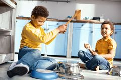 Pleasant little boys playing music on saucepans. Little music lovers. Upbeat little boys playing music on saucepans with wooden spoons and having fun while Stock Photography