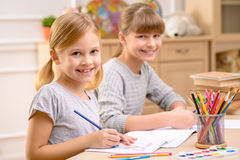 Pleasant little girl drawing stock images