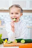 Pleasant little girl eating cucumber Stock Photo
