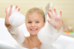 Pleasant little girl playing in bath tube. Express positivity. Selective focus of hands of cheerful little girl taking bath and having fun in the bath tube royalty free stock photography