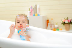 Pleasant little girl playing in bath tube. Happy childhood. Pleasant playful little girl blowing soap bubbles and having fun while taking bath royalty free stock photos
