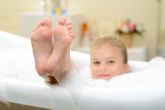 Pleasant little girl playing in bath tube. Happy moment. Selective focus of feet of pretty little girl lying in the bath tube while taking bath royalty free stock images