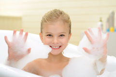 Pleasant little girl playing in bath tube. Joyful mood. Pleasant smiling little girl playing with foam and resting while taking bath stock photos