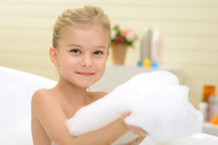 Pleasant little girl playing in bath tube. Like taking bath. Little cheerful pretty girl sitting in the bath tube and expressing joy while playing with foam stock photos