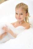 Pleasant little girl playing in bath tube. Take care of yourself. Pleasant content little girl lying in the bath tube and feeling happy while taking bath stock photo