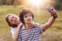 Pleasant looking female and male have happy expressions, pose for making selfie in modern smart phone, have good relationship, use. Modern technology. Couple of Stock Images