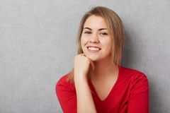 Pleasant looking pleased female has pleasant smile, demonstrates white perfect teeth, keeps hand under chin, being glad to be phot stock image