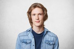 Pleasant looking stylish male with trendy hairdo, wears denim shirt, looks seriously directly into camera, isolated over white con. Crete background. Male Royalty Free Stock Images