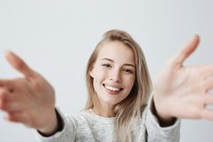 Pleasant-looking young Caucasian woman with broad smile showing straight white teeth, happy to meet friends, stretching. Headshot of pleasant-looking young Stock Photos