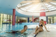 Pleasant loving couple resting near swimming pool royalty free stock images