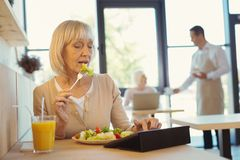 Nice elderly woman eating a salad. Pleasant lunch. Nice pleasant elderly women sitting at the table and eating a salad while using a tablet Royalty Free Stock Image