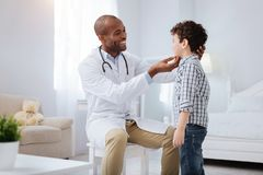 Pleasant male doctor checking boys tonsils. Regular examination. Cheerful gay male doctor looking at boy who standing in profile and checking his throat royalty free stock images