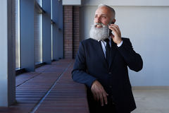 Pleasant male with grey beard talking on phone while leaning on Stock Photography