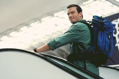 Pleasant male traveler is expressing gladness. Enjoying trip. Cheerful young guy with backpack is standing on moving staircase at modern airport while looking at royalty free stock image