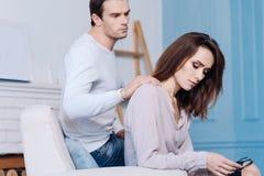 Pleasant man comforting his gloomy wife Royalty Free Stock Photo