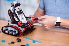 Pleasant man constructing robot. Royalty Free Stock Photo