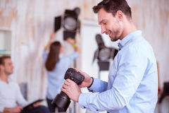 Pleasant man holding photo camera. Like my occupation. Pleasant smiling delighted handsome men holding photo camera and working in photo studio while expressing stock photography