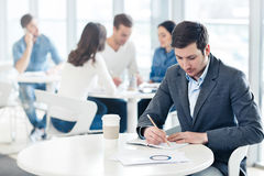 Pleasant man sitting at the table Stock Photos