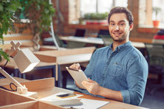 Pleasant man sitting at the table. My workplace. Smiling positive content man using tablet and expressing gladness while sitting at the table royalty free stock images