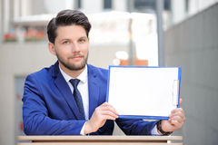 Pleasant man sitting at table with papers Stock Photos