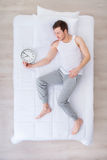 Pleasant man sleeping with clock royalty free stock photo