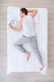 Pleasant man sleeping with clock royalty free stock photos