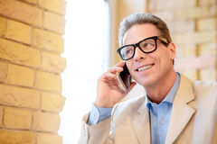 Pleasant man talking on mobile phone Stock Image