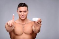 Pleasant man using cream Stock Image