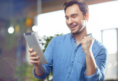 Pleasant man using tablet. I am the winner. Positive pleasant handsome man holding tablet and using it while expressing jubilation royalty free stock photography