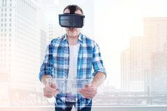 Pleasant man in VR headset having transparent tablet. Nice pastime. Handsome young man in a checkered shirt wearing a VR headset and holding a transparent tablet Royalty Free Stock Image