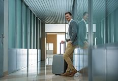 Pleasant man is waiting for flight with luggage. Full of joy. Full length of elegant young delighted businessman is standing with suitcase and leaning on wall Stock Image