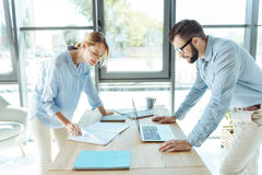 Pleasant man and woman working together in the office Stock Image