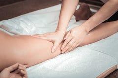 Professional female masseuse touching her clients leg. Pleasant massage. Professional female masseuse touching her clients leg while doing professional massage stock photography