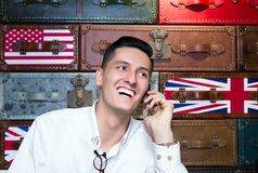 Pleasant mobile chat. Portrait of a young man talking on a mobile phone and laughing. English-style leather suitcases texture in the background Royalty Free Stock Images