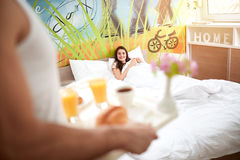Pleasant morning together in bed. Male surprised female for Valentine`s day with breakfast in bed Stock Photo