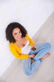 Pleasant mulatto woman sitting on the floor Stock Image