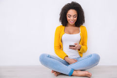 Pleasant mulatto woman sitting on the floor. Get in touch. Cheerful pleasant mulatto woman holding mobile phone and smiling while sitting on the floor Stock Images