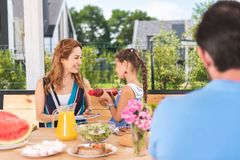 Pleasant nice girl offering ketchup to her mother. Would you like some. Pleasant nice girl smiling while offering ketchup to her mother Stock Images