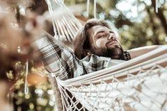 Pleasant nice man sleeping in a hammock