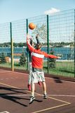 Pleasant nice men throwing each other the ball. Basketball team. Pleasant nice men throwing each other the ball while practicing basketball royalty free stock image