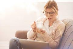 Pleasant nice woman having tea Stock Image